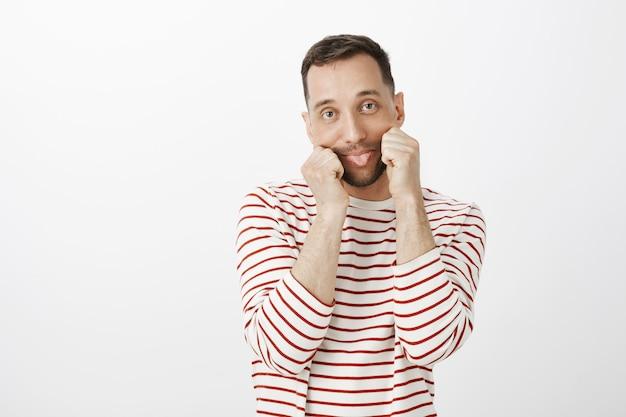 縞模様の服で遊び心のある幼稚な白人の男の肖像、手で口を引っ張って、無関心な退屈な表情で舌を突き出す