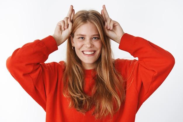 Портрет игривой, забавной и харизматичной молодой девушки с милыми веснушками и голубыми глазами, показывающими рога с указательными пальцами на голове, радостно улыбающимися, упрямыми и креативными над серой стеной