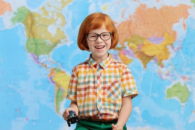 遊び心のある赤い髪の小さな男の子のカラフルな服を着て、おもちゃの車を手に持って、幼稚園に行きながら気分が良い。世界地図に対してポーズ面白い赤毛の少年。子供と学校