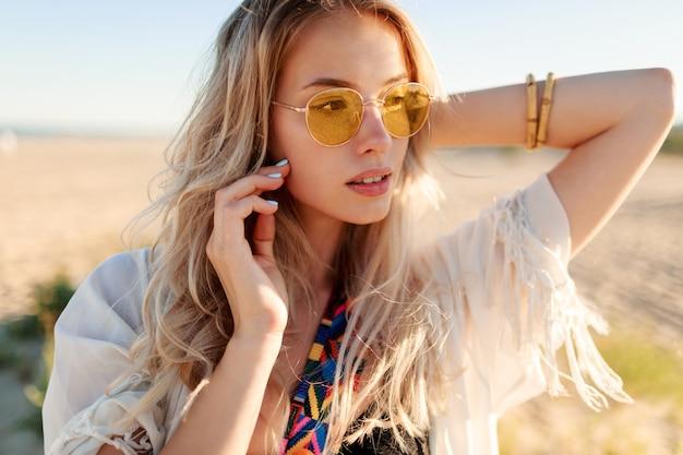 머리카락을 가지고 노는, 재미와 해변에서 여름을 즐기는 장난 웃는 금발 소녀의 초상화.