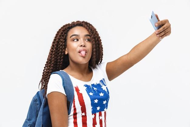 白い壁に隔離されて立っている間笑顔で携帯電話でselfie写真を撮るバックパックを身に着けている遊び心のある女性の肖像画