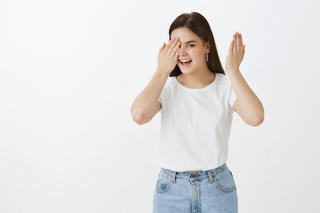 Портрет игривой молодой женщины позирует у белой стены