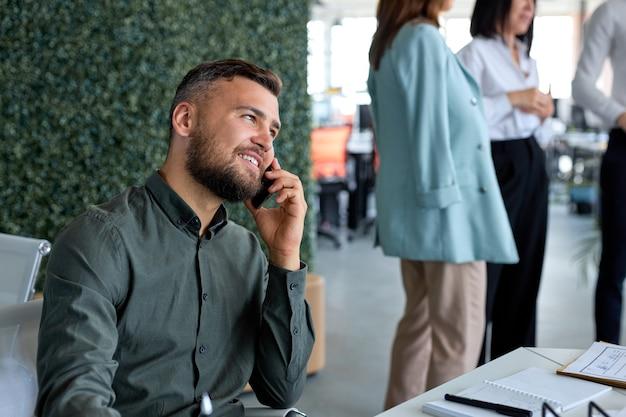 オフィスで電話で話している笑顔の楽しい白人の魅力的な男の肖像画、側面図の肖像画。ビジネスコンセプト。会話をしている男。フリーランス、スマートワーキング、テレワーキング。コピースペース