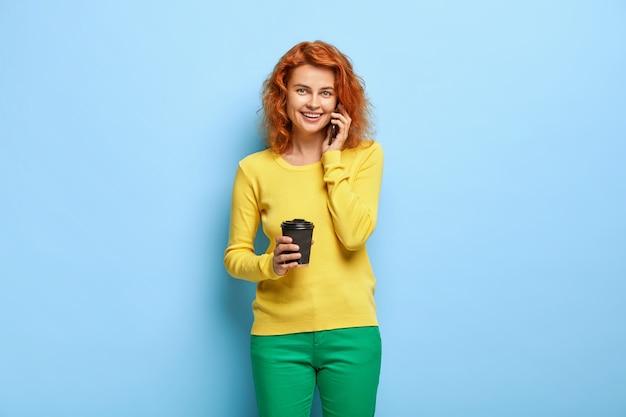 見栄えの良いセクシーな女性の肖像画は、コーヒーを飲み、スマートフォンを介して呼び出します