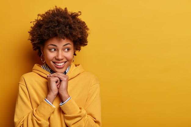 Портрет приятной на вид женщины с кудрявыми волосами, радостно смотрит в сторону, в приподнятом настроении, одетая в толстовку, позирует на фоне желтой стены. концепция выражения человеческого лица и эмоций