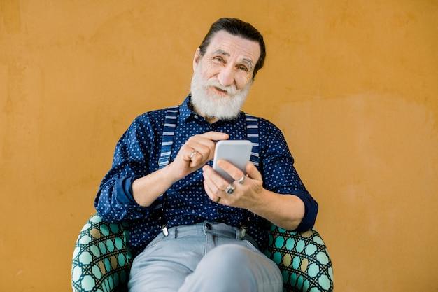 Портрет приятного старшего улыбающегося бородатого мужчины, одетого в стильную рубашку и брюки, сидящего на желтом фоне и использующего телефон