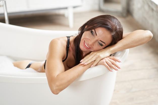 お風呂で喜びを取って快適な女性の肖像画