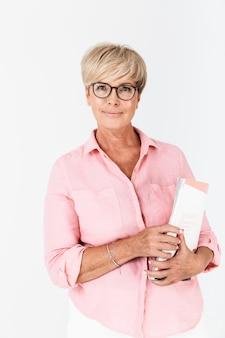 Портрет довольной взрослой женщины в очках, держащей учебную книгу, изолированную над белой стеной в студии