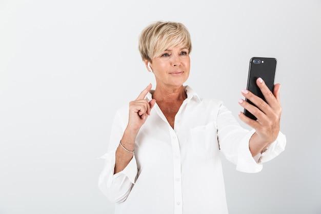 スタジオで白い壁に隔離されたイヤポッドと携帯電話を使用して短いブロンドの髪を持つ満足している大人の女性の肖像画