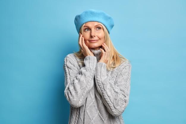 喜んでいる夢のような女性の肖像画が顔に優しく目をそらし、穏やかな表情でベレー帽のグレーのニットセーターを着ています。
