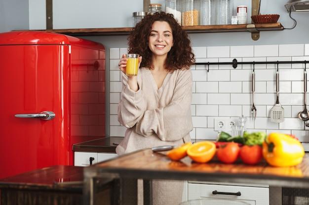 Портрет довольной европейской женщины, пьющей свежий апельсиновый сок во время приготовления овощного салата в интерьере кухни дома