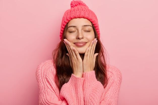 満足しているヨーロッパの女性の肖像画は、手のひらで両方の頬に触れ、ニット帽とセーターを着て、満足して目を閉じます