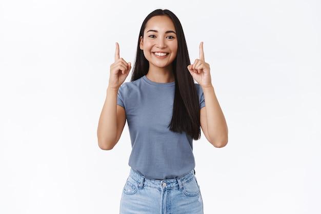 Портрет довольной красивой восторженной азиатской женщины в футболке, поднимающей руки и указывающей пальцами вверх, чтобы продвигать и побуждать клиентов останавливаться по нажатой ссылке, подписываться на ее страницу, улыбаясь