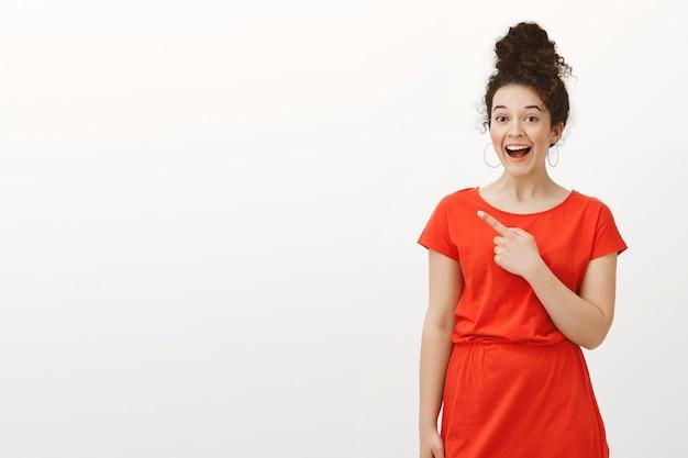 롤빵 헤어 스타일에 곱슬 머리와 빨간 드레스에 기쁘게 행복 한 젊은 여자의 초상화