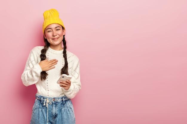 기뻐하는 한국 여성의 초상화는 가슴에 손바닥을 두르고 따뜻한 말에 감동하고 현대 전자 장치를 들고 노란색 모자, 캐주얼 흰색 점퍼 및 청바지를 착용합니다.