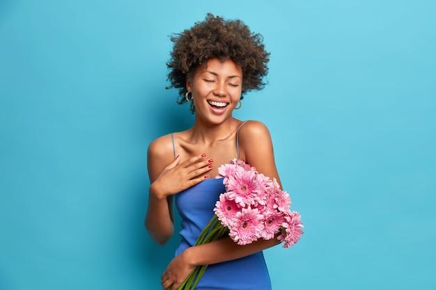 喜んで誠実な女性の肖像画は、ガーベラの花の美しい花束を心地よく保持し、青い壁に隔離されたドレスを着ています