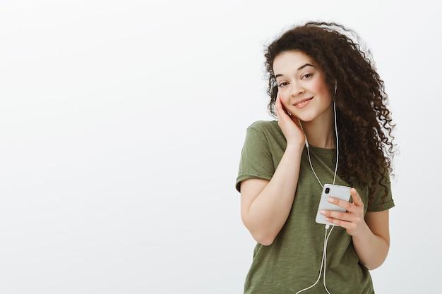 Портрет довольной нежной подруги с вьющимися волосами, наклонившей голову и держащей наушник в ухе, слушая отличную музыку в смартфоне