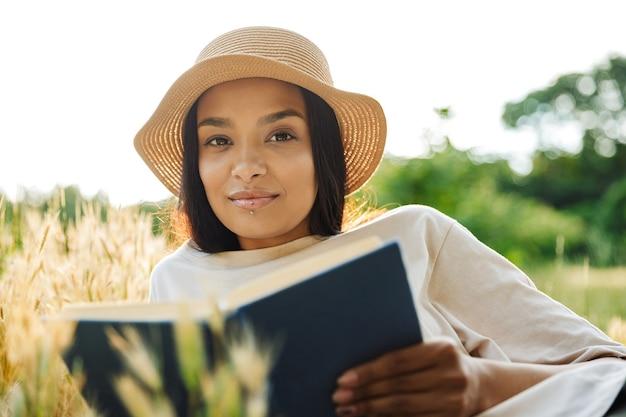 Портрет довольной женщины с пирсингом в губе и соломенной шляпе, читающей книгу, лежа на траве в зеленом парке