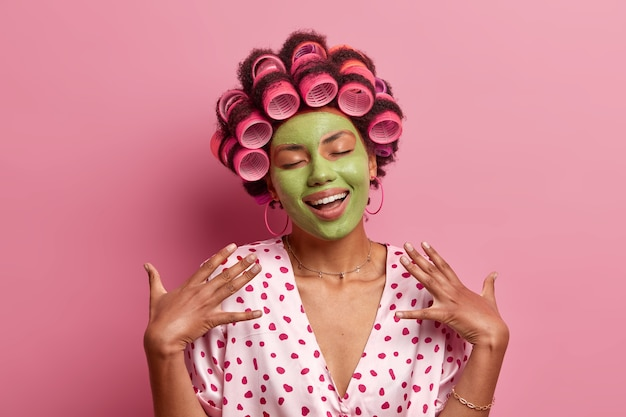 Портрет довольной молодой афро-американской женщины стоит с закрытыми глазами, нежно улыбается, воображает что-то приятное, применяет зеленую маску для лица, бигуди, стоит в помещении
