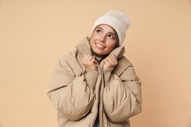 Портрет довольной молодой женщины в зимнем пальто, улыбающейся и смотрящей вверх