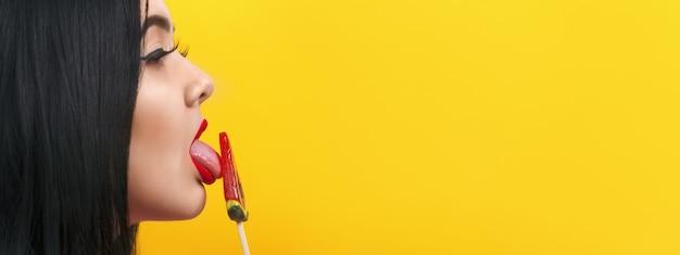 Портрет модели больших размеров в профиль с изображением леденца на желтом фоне