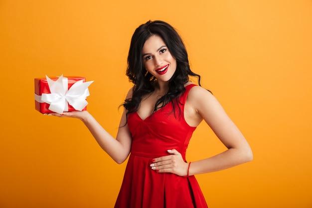 선물 포장 선물 상자와 함께 선물 상자를 들고 빨간 드레스에 포 쉬 매력적인 여자 20의 초상화, 노란색 벽 위에 절연