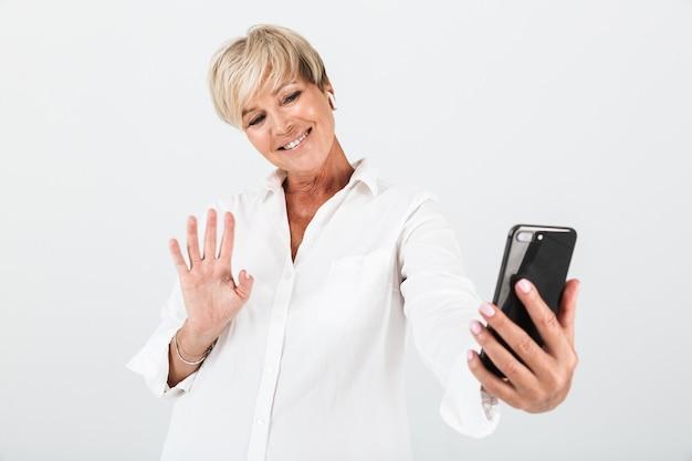 イヤポッドを使用し、スタジオの白い壁に隔離された携帯電話で手を振って短いブロンドの髪を持つポジティブな大人の女性の肖像画