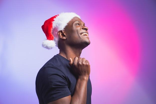 カラフルな背景、クリスマスの時期にサンタの帽子とカジュアルなtシャツでポジティブなアフリカ系アメリカ人の笑顔の男の肖像画。冬の休日と感情的な人々の概念。