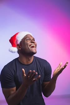 カラフルなサンタの帽子とカジュアルなtシャツの肯定的なアフリカ系アメリカ人の笑顔の男の肖像画