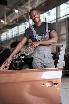 Портрет позитивного афро-американского автомеханика в униформе, позирующего после работы