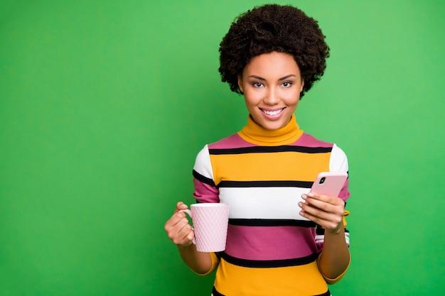 Портрет позитивной афро-американской девушки-блогера, которая наслаждается осенними каникулами, пользуется мобильным телефоном, следит за публикацией репоста, комментирует, держит кружку с горячим напитком, носит яркий блестящий наряд