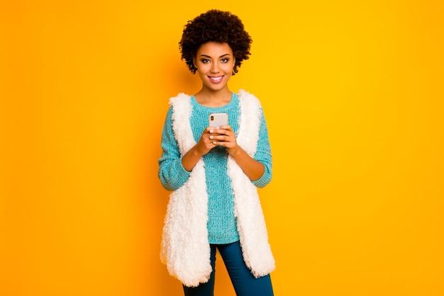 Портрет позитивной афро-американской девушки, использующей смартфон, следите за комментариями блоггеров, постите, носить бирюзовый свитер, белый пушистый стильный модный жилет, синие брюки, брюки, изолированные на стене яркого цвета