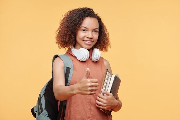 Портрет позитивной афро-американской студентки с вьющимися волосами, держащей книги и показывающей большой палец вверх на желтом фоне