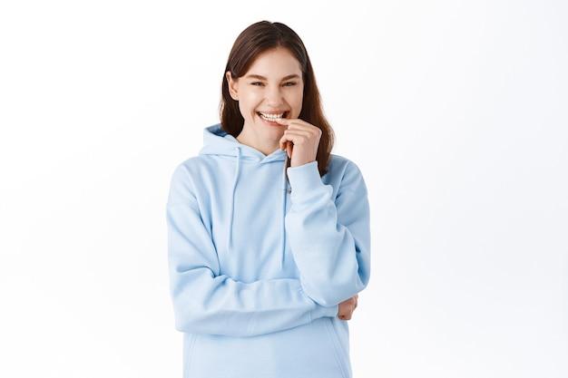 후드티를 입은 긍정적이고 귀여운 젊은 여성의 초상화, 웃고 웃고, 밝은 흰색 미소로 입술을 만지고, 스튜디오 벽에 기대어 서 있습니다.