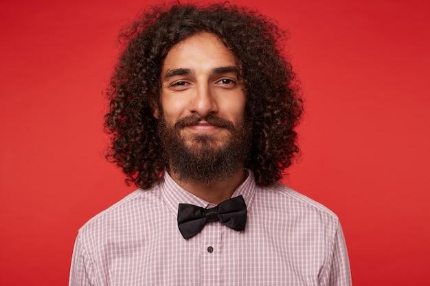 포즈를 취하는 동안 체크 무늬 셔츠와 검은 나비 넥타이를 착용하고 수염을 가진 긍정적 인 매력적인 갈색 머리 곱슬 남자의 초상화, 부드러운 미소로보고