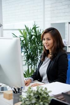 Plと彼女のオフィスの机でコンピューターでの作業を楽しんでいるポジティブな美しい実業家の肖像画...