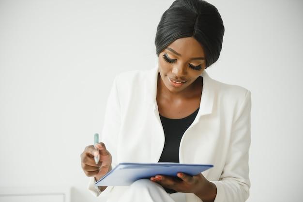 사무실에서 상담하는 동안 메모를 하는 긍정적인 흑인 여성 심리학자의 초상화. 클립보드가 있는 소파에 앉아 병원에서 웃고 있는 성공적인 젊은 심리 치료사