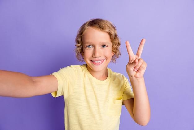 ポジティブな男の子の肖像画は、自分撮り写真を撮るv-signは、紫色の背景の上に分離された黄色のtシャツを着用する