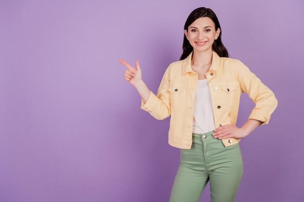 ポジティブなカジュアルな女の子の肖像画は、紫色の背景に指の空白スペースを示しています