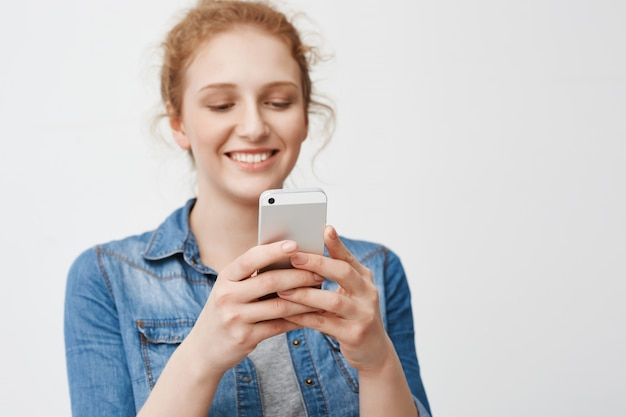 Портрет положительного очаровательная рыжая девушка с булочкой прическа чувственно улыбаясь, держа смартфон и текстовые сообщения