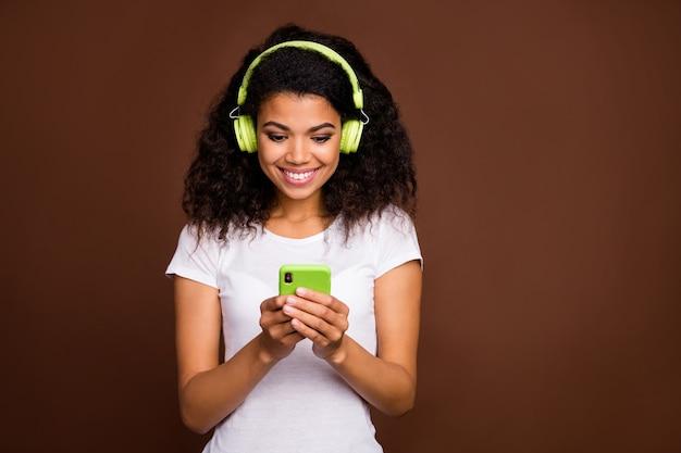 긍정적 인 쾌활한 아프리카 계 미국인 여자 사용 핸드폰의 초상화는 녹색 무선 헤드셋이 라디오 멜로디 검색 온라인 재생 목록을 듣고 싶어요.