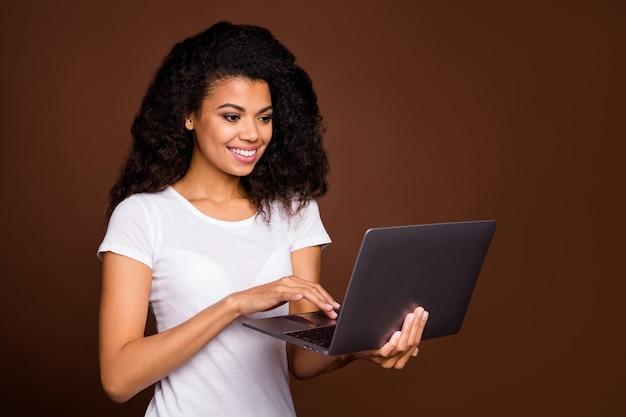Портрет позитивной жизнерадостной афро-американской девушки использует компьютерный поиск, читает новости социальных сетей, носит повседневную одежду.