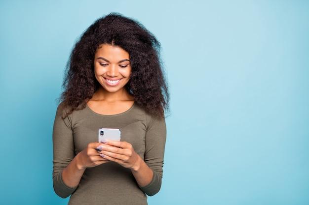 Портрет позитивной жизнерадостной афроамериканской девушки использует свой мобильный телефон, общается в сети в социальных сетях, читает ленту новостей, носит зеленый пуловер в повседневном стиле, изолированный на синей стене