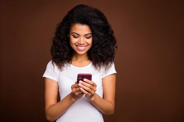 ポジティブで陽気なアフリカ系アメリカ人の女の子の肖像画は、スマートフォンを使用してソーシャルメディアのニュースを読んでください。