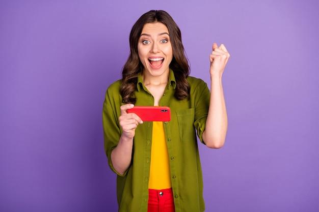 ポジティブで陽気な狂気の少女の肖像画は、スマートフォンを使用してソーシャルネットワークのビデオゲームをプレイし、勝利を祝う拳を叫ぶ紫色の背景の上に分離された流行の服を着る