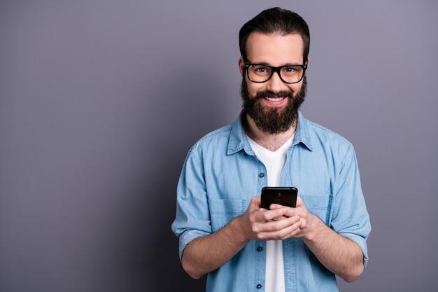 ポジティブで陽気なフリーランサーの男のブロガーの肖像画は携帯電話を使用しますソーシャルメディア情報を読む灰色の壁に隔離されたスタイリッシュなジーンズデニムの服を着