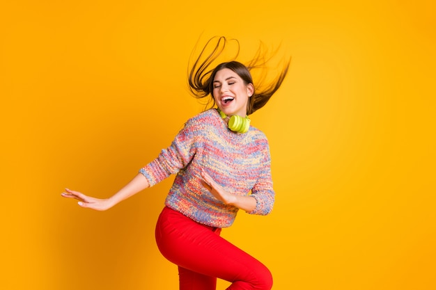 ポジティブで陽気なファンキーな女の子の肖像画は、ヘッドフォンで音楽を聴き、ダンスを開始しますダンスフロアウェアプルオーバー赤いズボン輝きの色の上に分離されました