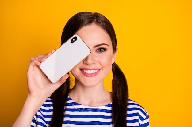 Портрет позитивной жизнерадостной девушки закрыть крышку мобильного телефона лицо глаза рекомендовать новый продукт объект устройства носить полосатую блузку, изолированную на блестящем цветном фоне