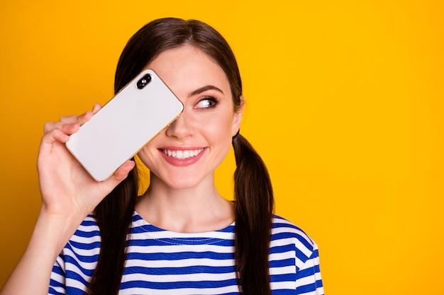 Портрет позитивной жизнерадостной девушки закрыть крышку смартфона лицо глаза указывают на современные технологии объект продукта носить полосатую блузку изолированный блеск цвет фона