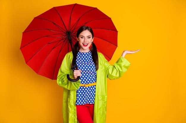 Портрет позитивной жизнерадостной девушки, наслаждающейся весенней прогулкой, держит красный зонтик, рука чувствует, что воображаемые капли дождя носят красивую одежду, изолированную на ярком блестящем цветном фоне